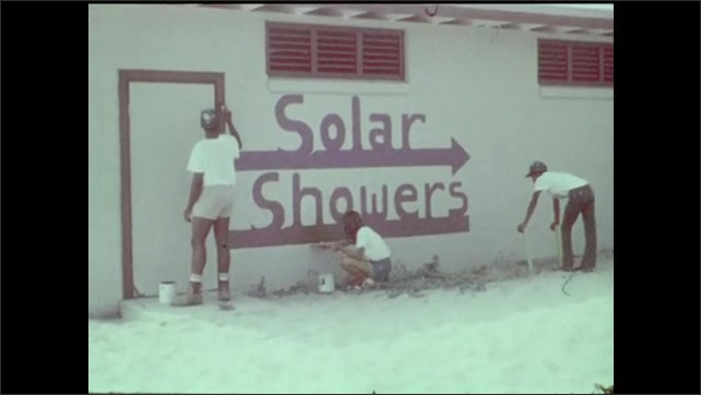 1970s: Workers build wooden structure frame near beach. Workers paint Solar Showers on exterior of building. Youth Conservation Corp workers finish Solar Shower building. Workers unbox heating tubes.