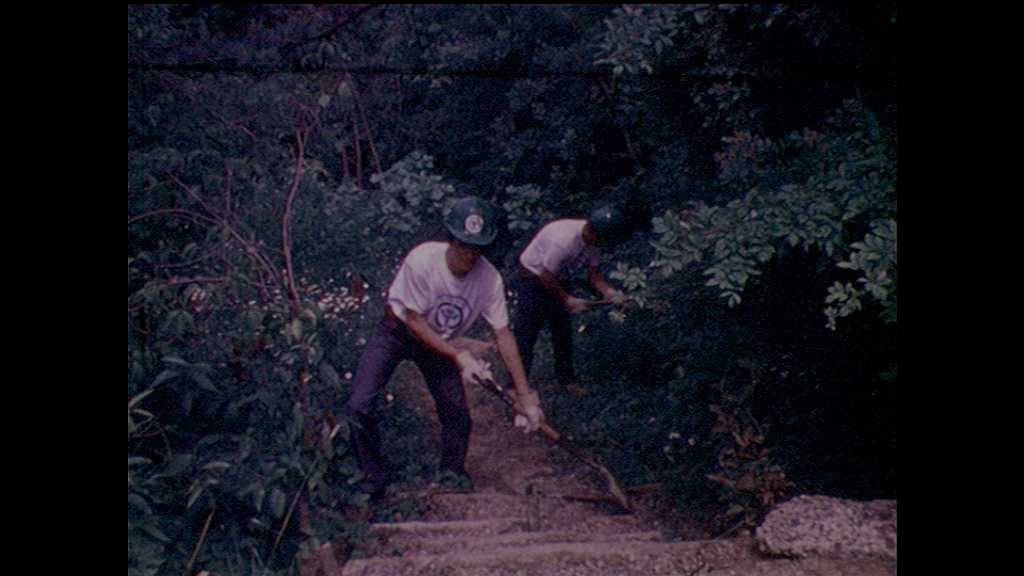 1970s: teenage boy scrapes shovel on dirt step. sign for Prince William Forest Park. boys and girls fill wheelbarrows and dump dirt near stream bank. workers sit on outdoor shelter and build roof.