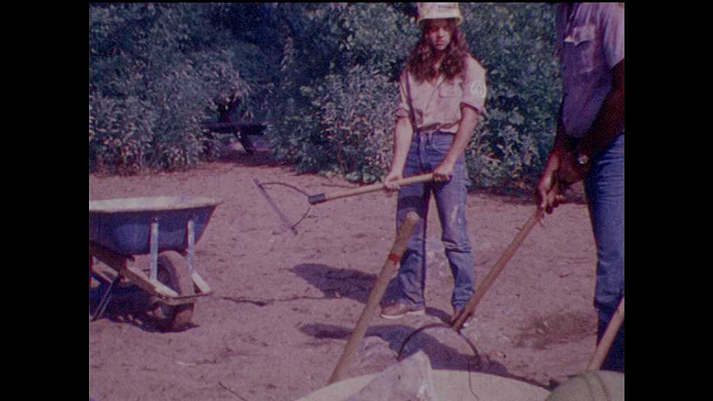 1970s: man and teenage girl practice swinging weed cutter as boys and girls watch in gallery. woman in wheelchair sits near bucket as talks. sign marks entrance to Fairy Stone State Park in Virginia.