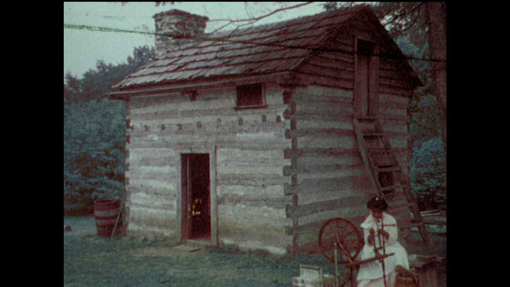 1970s: woman sits at spinning wheel by historic farmhouse while men and woman work in farm field with scarecrow. teenage boys and girls sit on ground and listen to man in hardhat near old building.