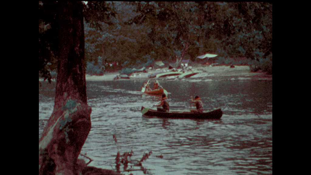 1970s: Canoes on the river. Canvas tents. Teens make camp on a riverbank. Girl grills over fire. Woman lands canoe on river bank and picks up litter on bank.