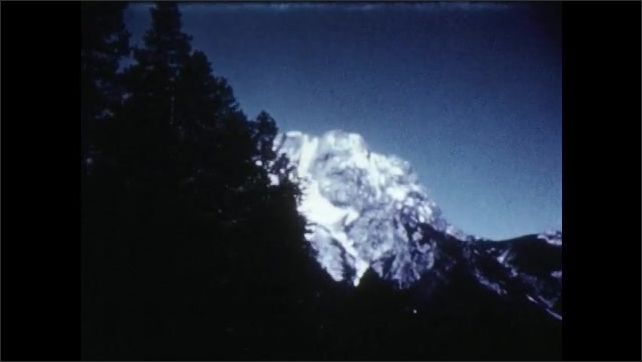 1950s: Forest, trees, snow capped mountain peak. Animation of water wheel in water.