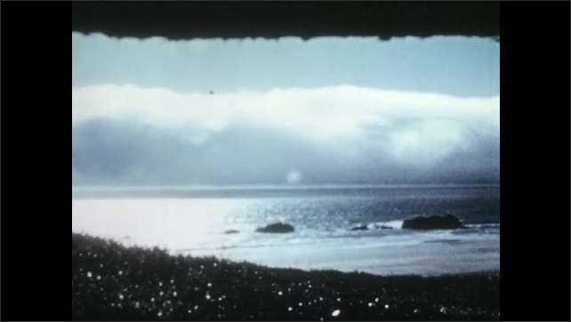1950s: Ocean and rocks. Clouds over the ocean. Water glides onto shore.