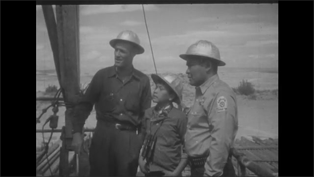 1950s: UNITED STATES: drilling rig in Utah. Hole in oil well. Workers at drilling rig in desert. Boy visits oil rig.