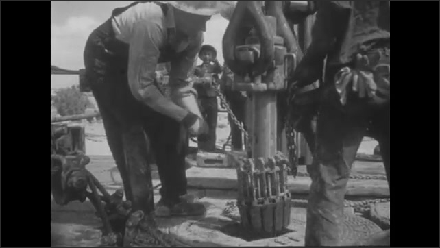 1950s: UNITED STATES: man works at oil well. Boy smiles. Boy visits oil well. Men drill for oil in desert.