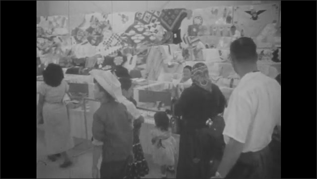 1950s: UNITED STATES: people arrive at exhibition hall. Navajo crafts on display. Fine Arts exhibition. Paintings on wall.