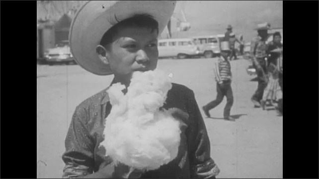 1950s: UNITED STATES: boy on fairground ride. Boy eats candy floss at fair. Boy on bike ride. Boy rides bike in street