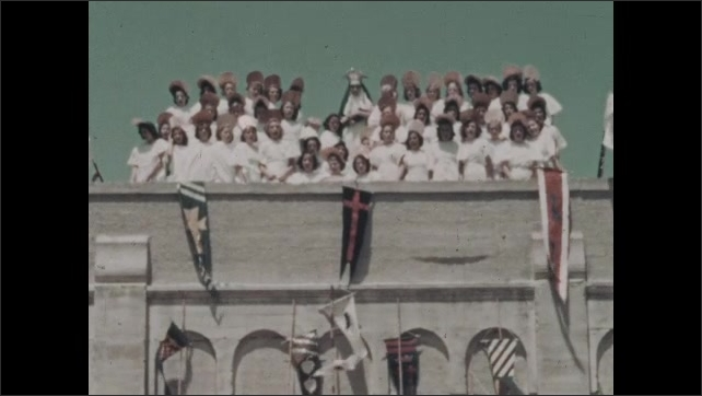 1930s: Group of girls wear white dresses, halo hats, stand with nun in crown on roof of building, flags, pennants.