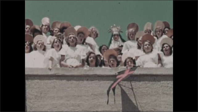 1930s: Group of girls wear white dresses, halo hats, sing, stand with nun on roof of building, flags, pennants. Nun wears crown, holds baby, smiles.