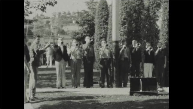 1930s: School.  Young men raise flag and play bugles.