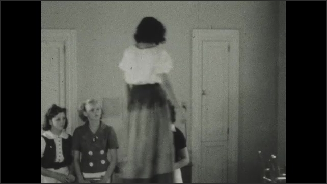 1930s: Girls adjust costumes on models. Students walk on table and model finished costumes.