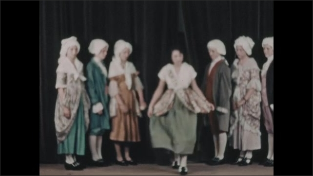 1930s: Boys and girls in colonial costumes stand on stage. Boys open curtains and girls with sashes emerge and curtsy.