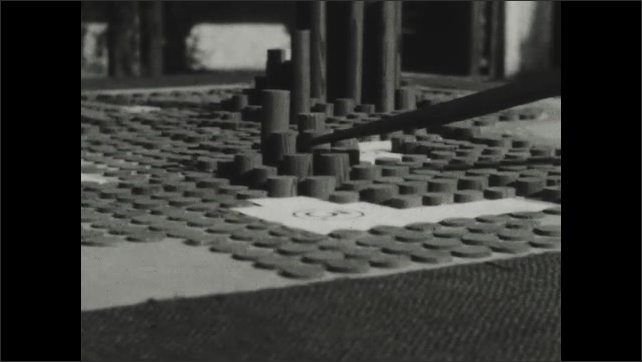1930s: Cylinders of various heights are situated like the layout of a city. Pointer points at couple of cylinder towers.