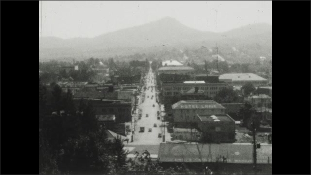 1930s: Main street of town with cars driving down both sides.