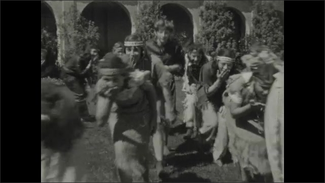 1930s: Young women dressed up as Native Americans run across lawn, bounce hands in front of their mouths. Group of women pose together outside.