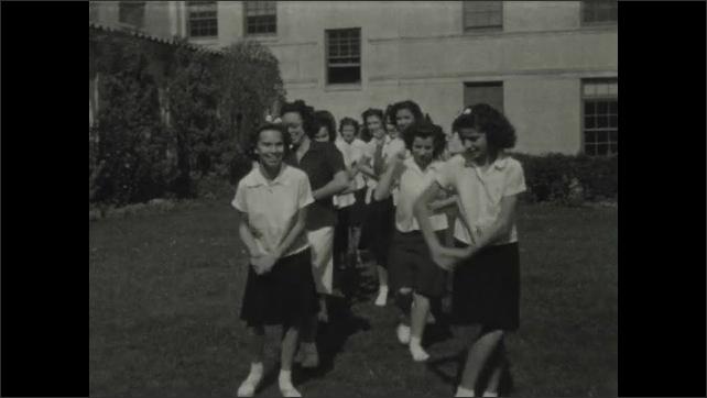 1930s: Young women in uniform dance across lawn.