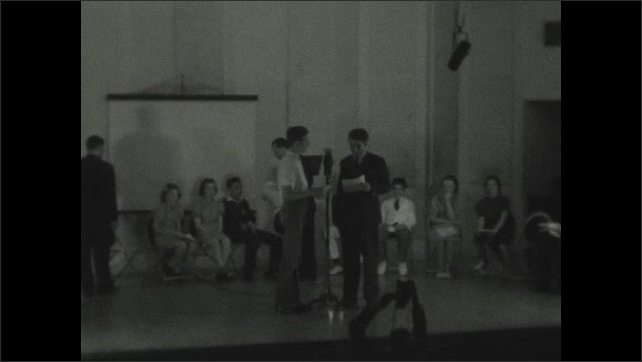 1930s: People on stage. Men stand at microphone, talk. People sit in chairs at back of stage.