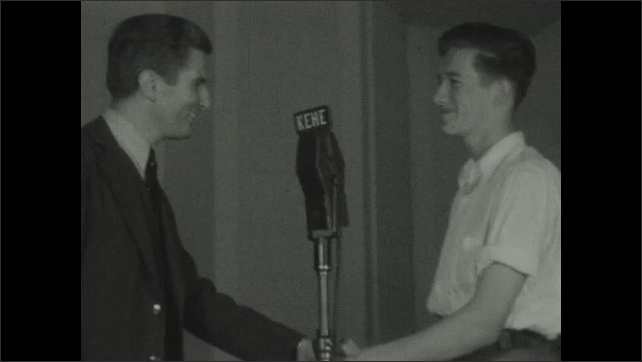 1930s: Young man walks up to man standing at microphone, they shake hands and talk.