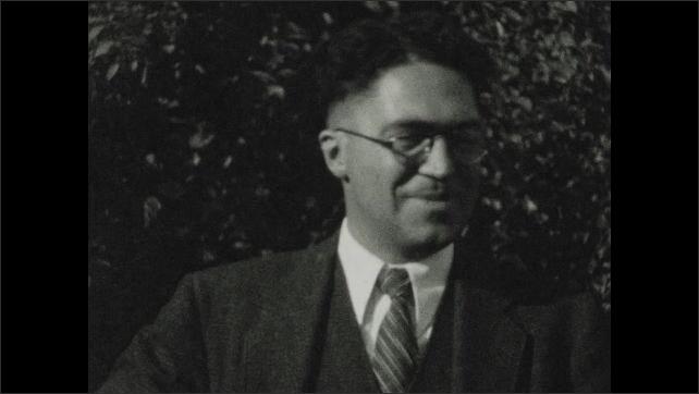 1930s: Man stands outside, holds up keys, smiles, talks.