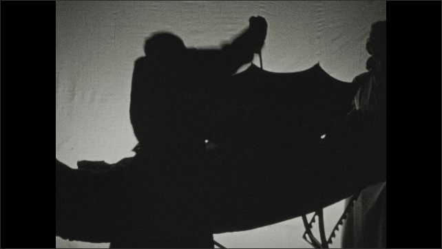 1930s: Silhouette of a doctor next to a patient on an operating table. Nurse hands the doctor an umbrella. Doctor pushes the umbrella into the chest of the patient, then closes the umbrella.