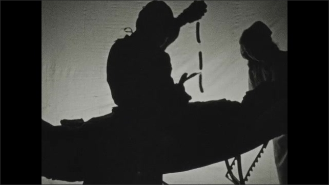 1930s: Silhouette of a doctor operating on a patient. Doctor pulls out what looks like 3 linked sausages and brandishes scissors. Doctor cuts sausages off in their connectors, one by one.