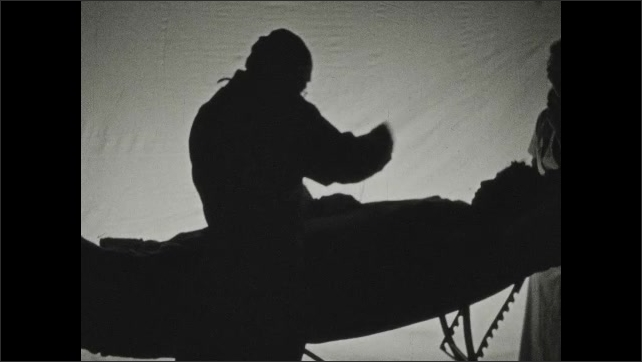 1930s: Silhouette of a doctor sewing a patient using a large needle and thread. Nurse wipes the forehead of the patient on the table.