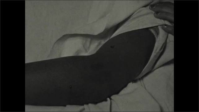 1930s: Doctor pushes the oversized syringe into the patients arm. When the needle is removed, a large hole is left in the patients arm. Doctor and nurse cover the patients head with a white sheet.