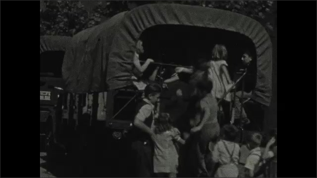 1930s: Group of nurses and doctor holding the syringe run down the street. Large group of children load on to a covered wagon school bus.