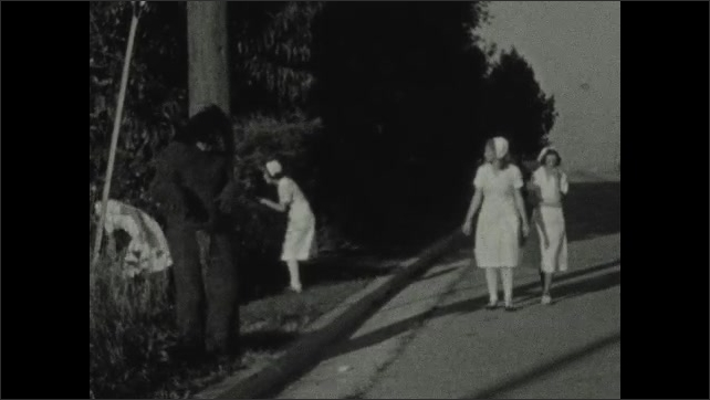 1930s: The doctor and nurses search the bushes on the side of the road as the monster hides behind a pole. The monster comes out from behind the pole and the doctor and nurses run away in fear.