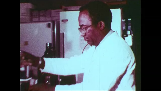 1970s: United States: pipes at chemical works. Scientists work in laboratory. Man empties white powder into beaker