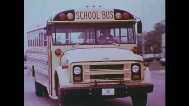 1970s: United States: grass in Iowa field. School bus on road. Solid waste plant. View across field
