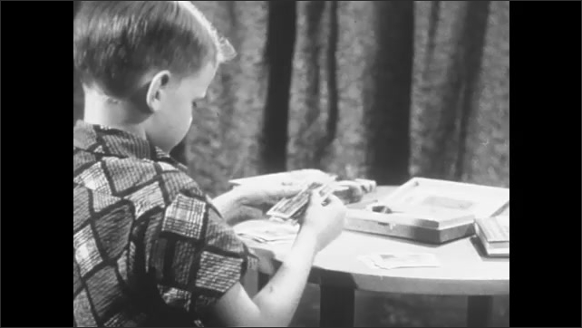 1950s: school child laying out photographs on a table, teacher using visuals aids to teach