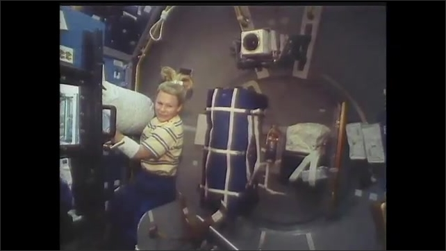 1990s: Astronauts working in spacecraft, man moving equipment. Woman with equipment. View over shoulder, man working with equipment in enclosed chamber.