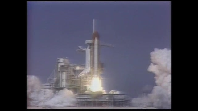 1990s: Rocket engines firing. Rocket lifts from launchpad. Rocket launching. View of Earth from space.