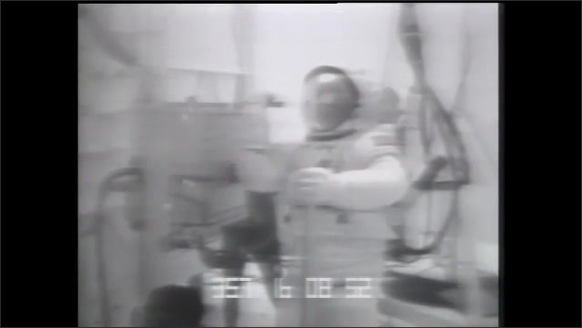 1990s: Feet on treadmill. Man walking on treadmill. Footage of man walking on monitor. Men watching monitor. Man at computer. Astronaut in space suit underwater. Man at computer. Graphics on screen.