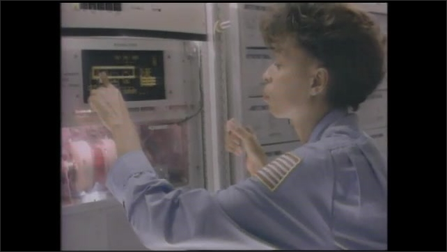 1990s: Man walking though lab, looks at plants. Hands pick up plant roots. Close up of hand with plant. Woman presses buttons on panel. Woman working in glove box. View of Earth from space.