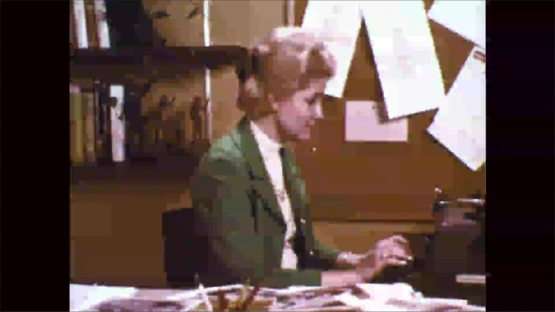 1960s: Woman sits at desk, looks at papers. Woman smiles, nods, types on typewriter.