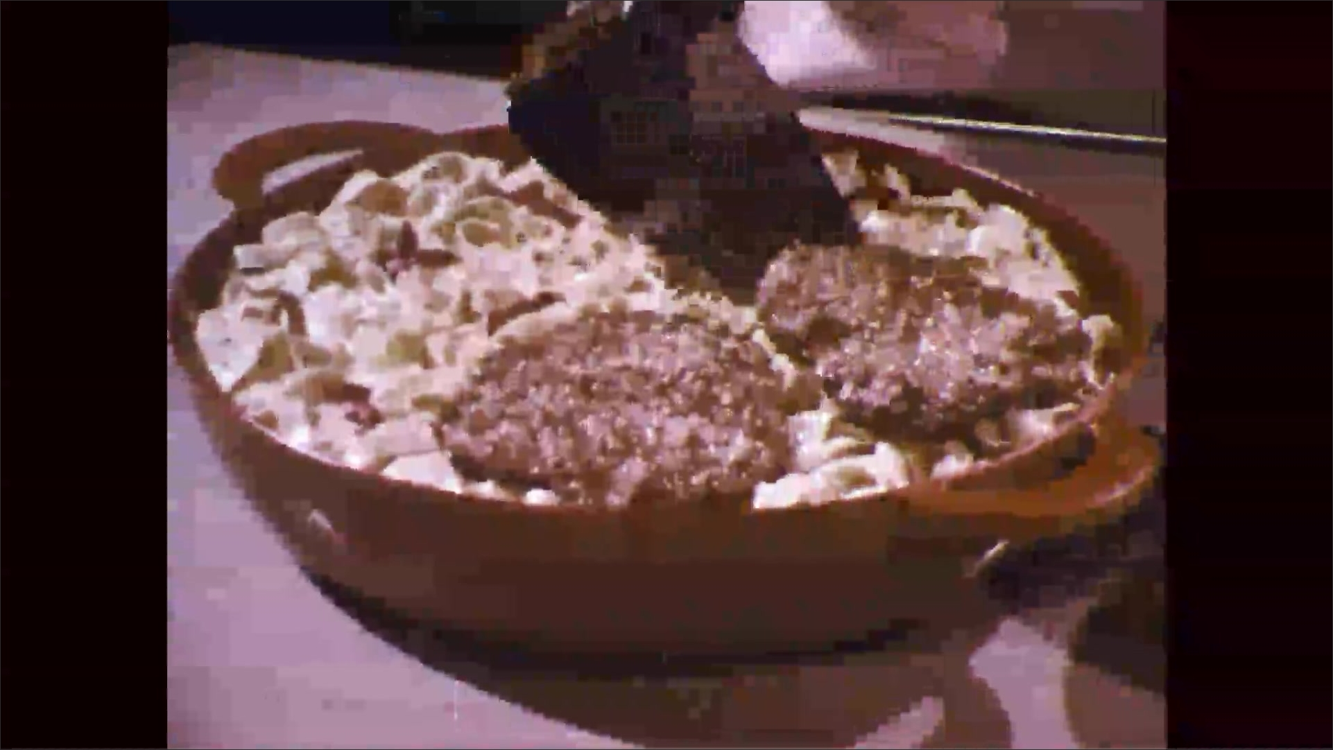 1960s: Woman takes porklets out of pan, places them on top of noodles in dish. Woman places dish of noodles and pork onto placemat.