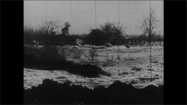 1930s: River floods over houses and property. Barren, dry land with mountains in distance.