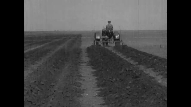 1930s: Man rides tractor, rototilling dirt, over field. Man rides rototilling tractor over dirt field.