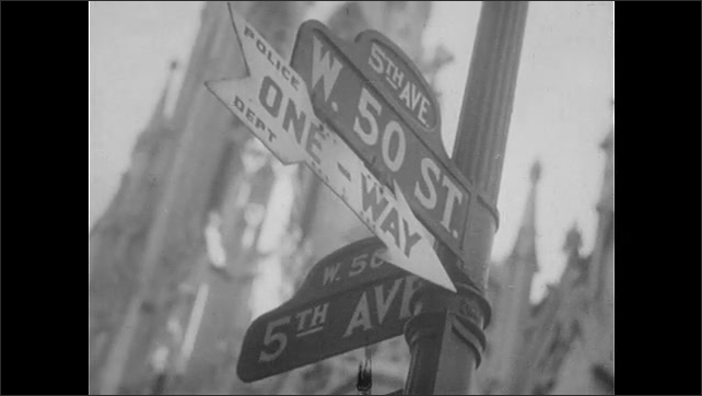 """1940s: City.  Street sign reads """"5TH AVE., W. 50TH ST.""""  Arrow reads """"ONE WAY, POLICE DEPT.""""  Massive crowd outside of St. Patrick's Cathedral.  Man takes photo."""