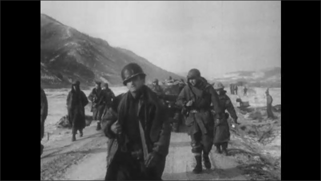 1950s: UNITED STATES: soldier in winter unit. Military vehicle follows soldiers along track. Unit crosses frozen ground. Soldiers carry supplies
