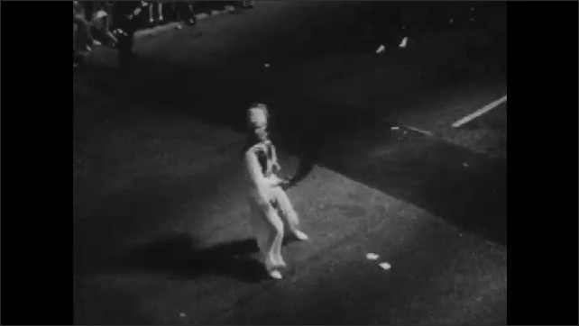 1950s: UNITED STATES: majorettes march in street at night. :ladies wave from float. Man dances in street. Carnival floats in street during Orange Bowl
