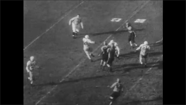 1950s: UNITED STATES: Miami team play in American football game. Man runs across pitch. Man runs with ball.