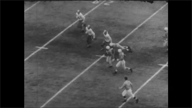 1950s: UNITED STATES: men line up in American football match. Player doges with ball. Players slide along ground. Men pass ball in match