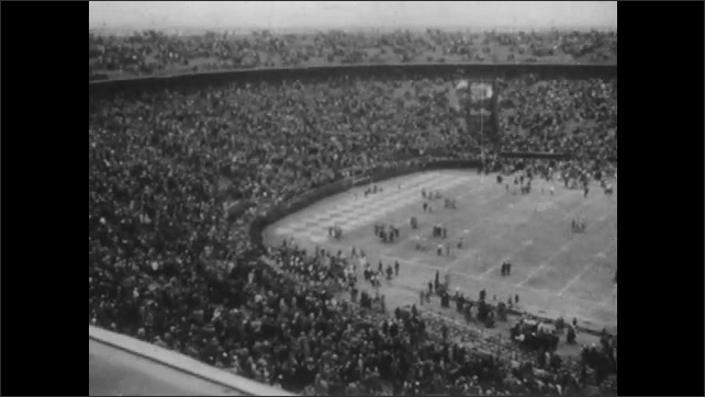 1950s: UNITED STATES: overhead view of crowd watching match. Kentucky team play Oklahoma at American football game.