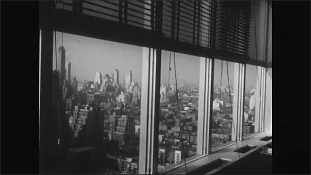 1950s: Man pushes filing cabinet through door inside building. Men move furniture through hall. Man sits at desk near window overlooking New York city. New York city.