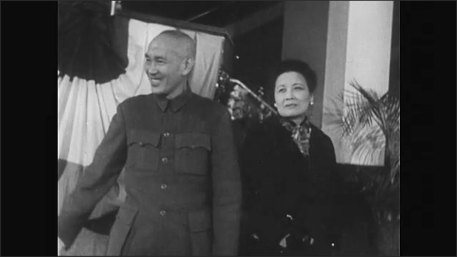 1950s: President Chiang Kai-shek walks in a cape up stairs. People stand in front of chairs in rows in room. Soong Mei-ling and Chiang Kai-shek stand, waving. Soldiers practice revelry.