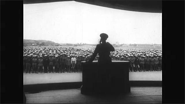 1950s: Male soldiers of Formosa practice revelry in formation. Female soldiers march in formation. Man stands at podium talking to large assembly. Man in uniform talking into mic. Audience salutes.