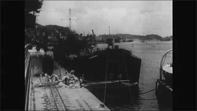 1950s: Man shakes hands of others. Soldiers stand by tanks, saluting. Official in jeep waves at soldiers lined in trucks. Official saluting. Village port. Workers unload boats at dock. Farmland.